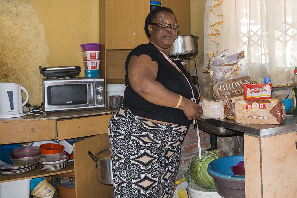 Tembe showing ingredients she uses for her beer making