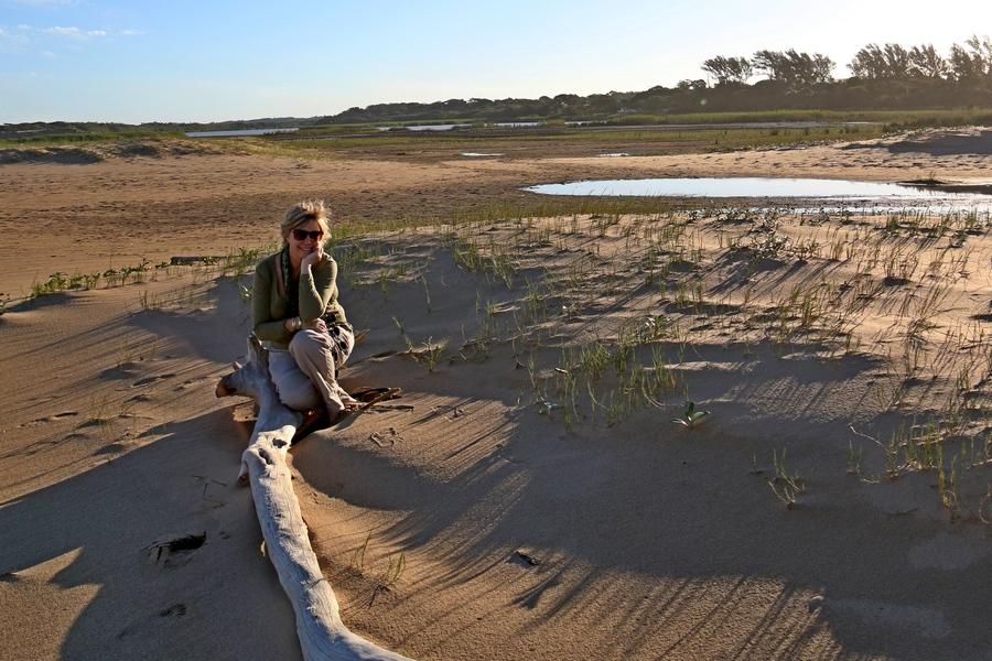 Cheryl sitting on log on beach